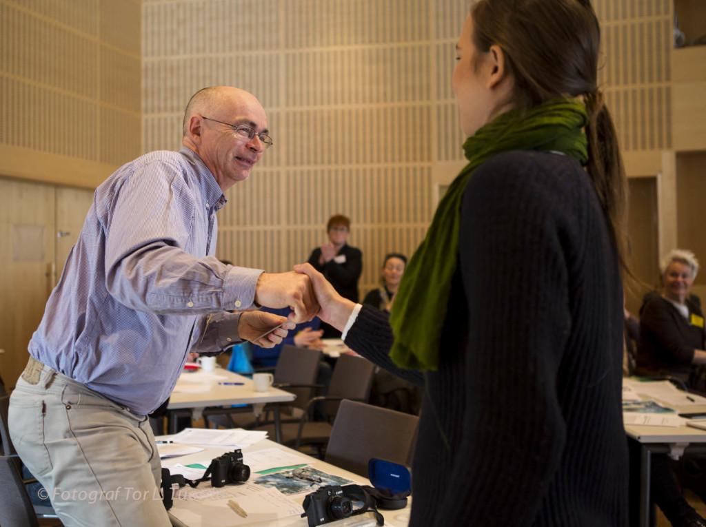 Urpo Taskinen får pris, en app, från länsordförandens hand.